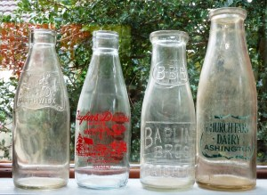 he two bottles on the right were closed with a circle of waxed card that pressed inside the rim of the wide neck.  That style of closure disappeared in the '50s, to be replaced by aluminium foil caps.